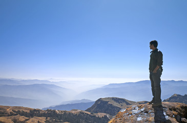 Man watching the layers of endless hills from the top of hill