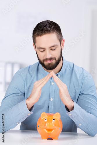 mann hält hände über sparschwein