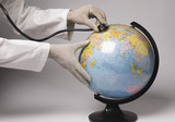 Close-up of human hands examining a globe with a stethoscope