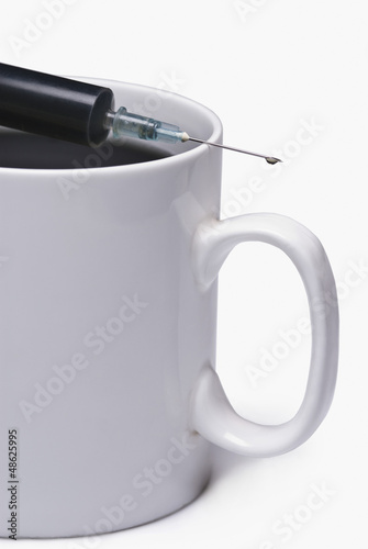 Coffee cup with a syringe