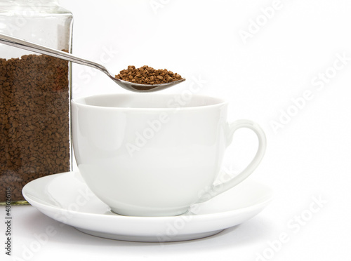 Spoon of instant coffee granules with cup and saucer and jar