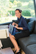 Young smiling woman sitting shopping bags couch
