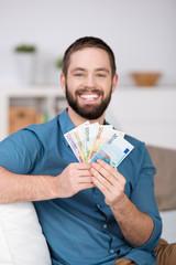 lachender mann zeigt geldscheine
