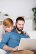 junges paar schaut auf laptop