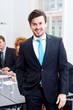 Erfogreicher Geschäftsmann lachend mit anzug und Krawatte mit K