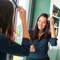 Young woman combing hair comb mirror bathroom