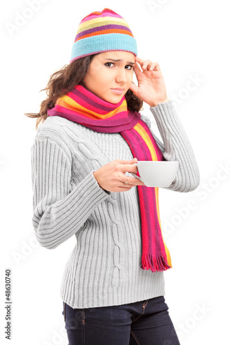 Young female having a headache and holding a cup of tea