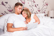 Mann und Frau im Bett beim kuscheln und surfen