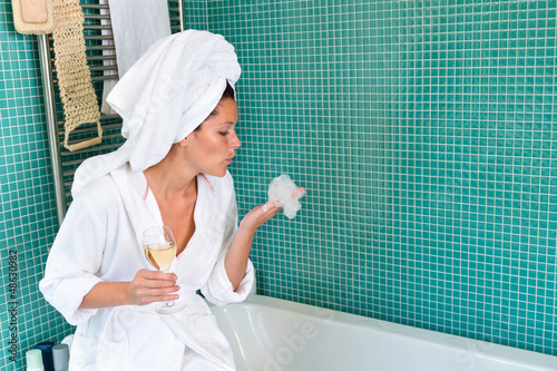 Young woman relaxing bathroom foam bathtub wine