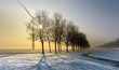 Bicycle track in a foggy wintry landscape with wind turbine