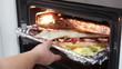 Mujer metiendo una merluza rellena en el horno
