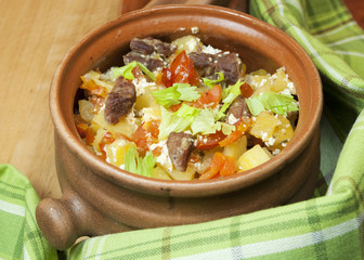Meat and vegetables with sour cream and green celery  in a pot