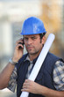 Construction worker on site with a phone
