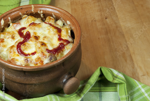 Meat and vegetables with cheese and ketchup  in a pot