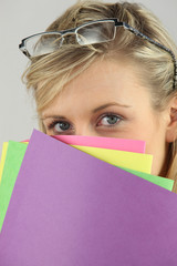 Blond woman covering her face with document folders