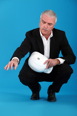 senior businessman holding a helmet