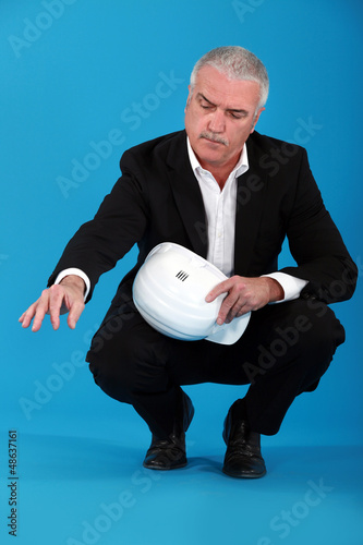 senior businessman holding a helmet