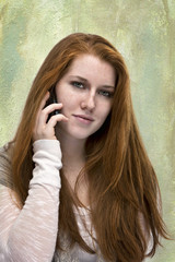 Beautiful red haired teen with phone
