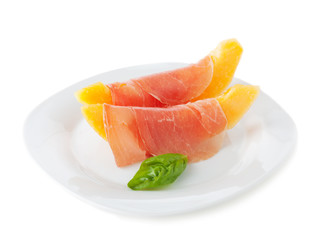Melon with prosciutto and basil on a plate