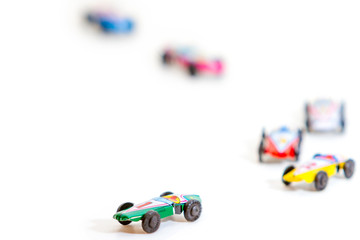 Colorful tin race cars on white background