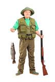 Mature hunter with shotgun holding a fish