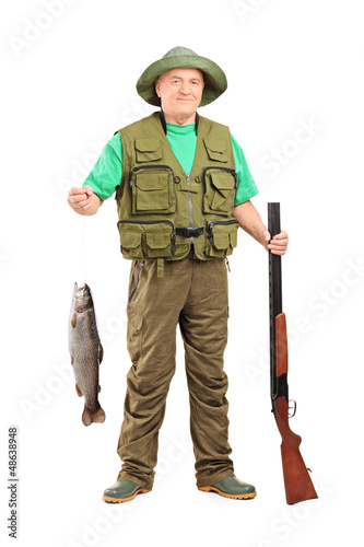 Mature hunter with shotgun holding a fish