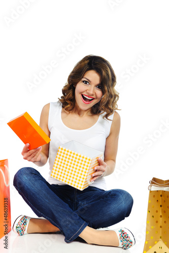 Excited young girl opening present box isolated on white