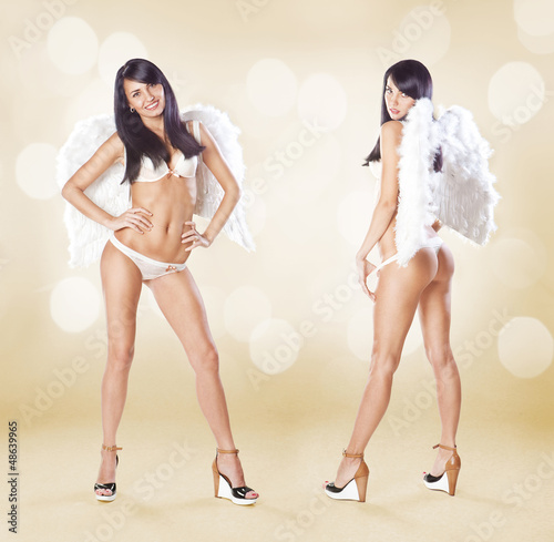 Two cute women angels standing with white wings and lingerie ove