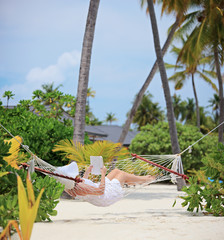Woman relaxing in a hammock, reading a book on a beach in Maldiv