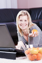 Cheerful woman using a laptop at home.