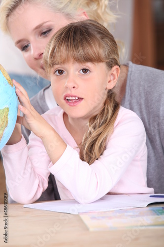 Little girl and mother looking at globe