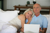 Middle-aged couple in bed with laptop poster