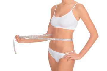 fit young woman measuring her waistline