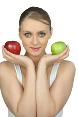 Young woman holding a red and a green apple