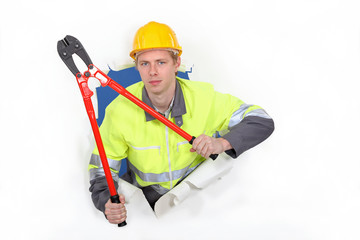 Man with bolt-cutters tearing through background