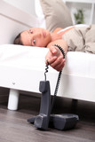 Woman laying in bed with house phone