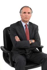Stern businessman sat in office chair