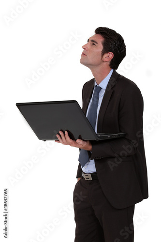 Businessman looking upwards and holding a laptop