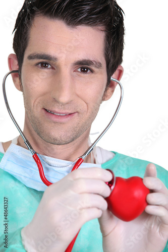 Young doctor listening to a model heart through a stethoscope
