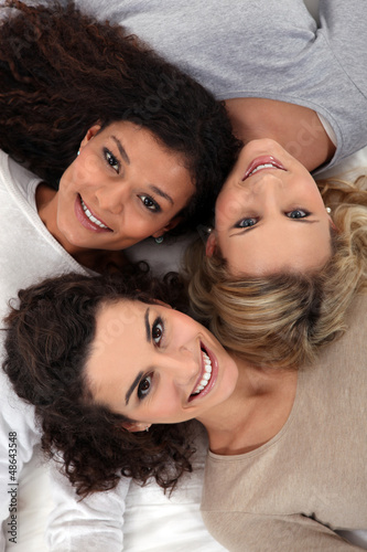 Three female friends laying together