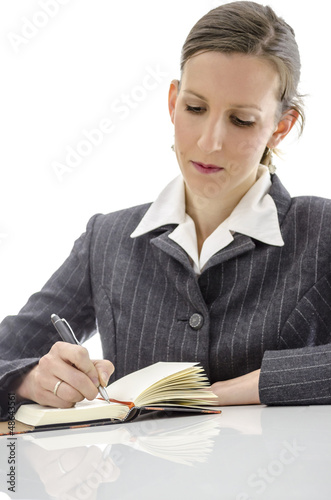 Businesswoman writing in her notepad