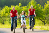Fototapety Family with kid cycling in summer with bicycles