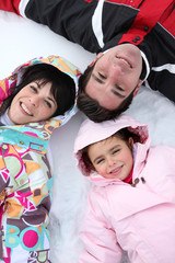 Family lying in the snow