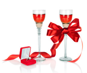 Wine in two wineglasses with red satin  bow and wedding rings in
