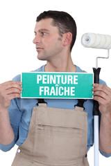 craftsman painter holding a ''wet paint'' label