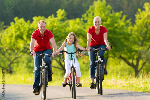 Family with kid cycling in summer with bicycles