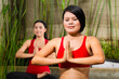 Asian women doing yoga in tropical setting