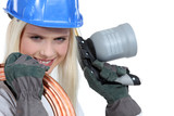 Blond woman with blowtorch and copper pipe poster