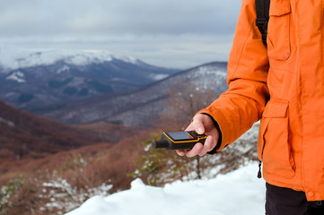 Backpacker holding in his hand GPS