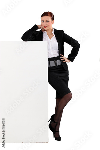 Attractive woman standing beside a blank sign
